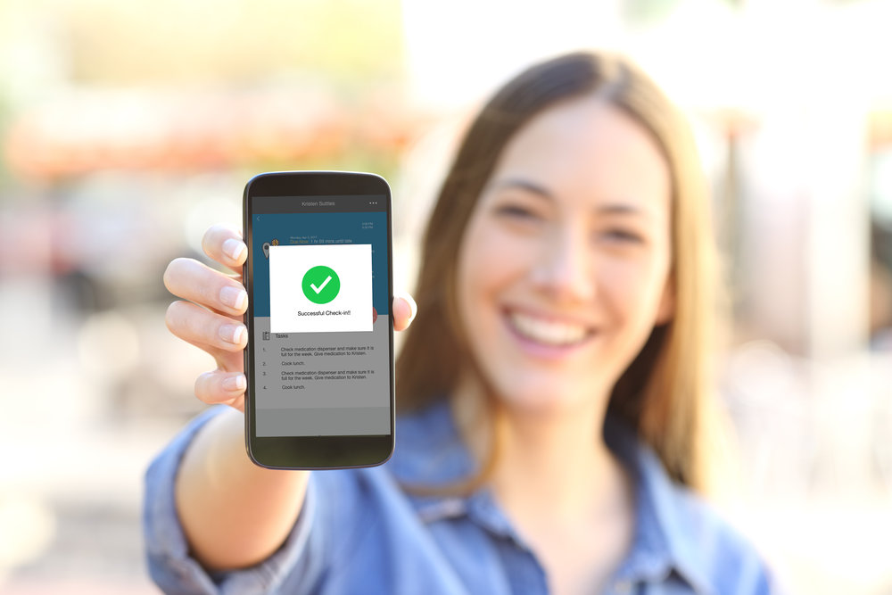A woman holds a phone with a graphic that says successful check-in.jpg