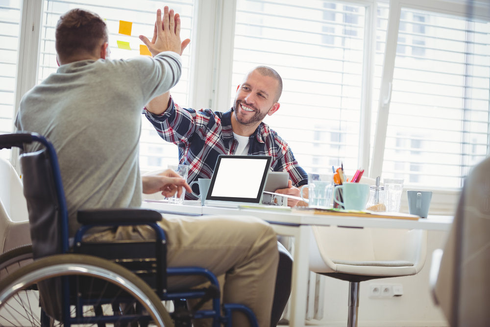 Image: A man using a wheelchair high-fives another man who is seated at a table with him. The man using the wheelchair is typing on a laptop. (Source: https://shutr.bz/2DxKM0i)