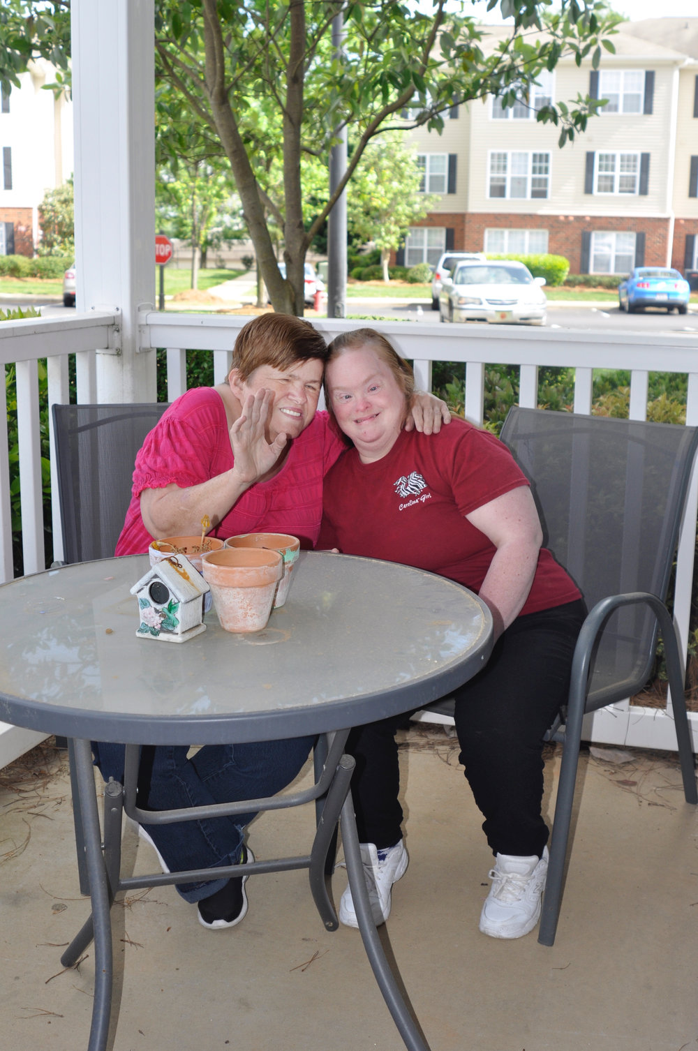 Image: Two women, Laura and Vicki, smile as they sit at a table. One of the women waves at the camera. (Source: SimplyHome photos)