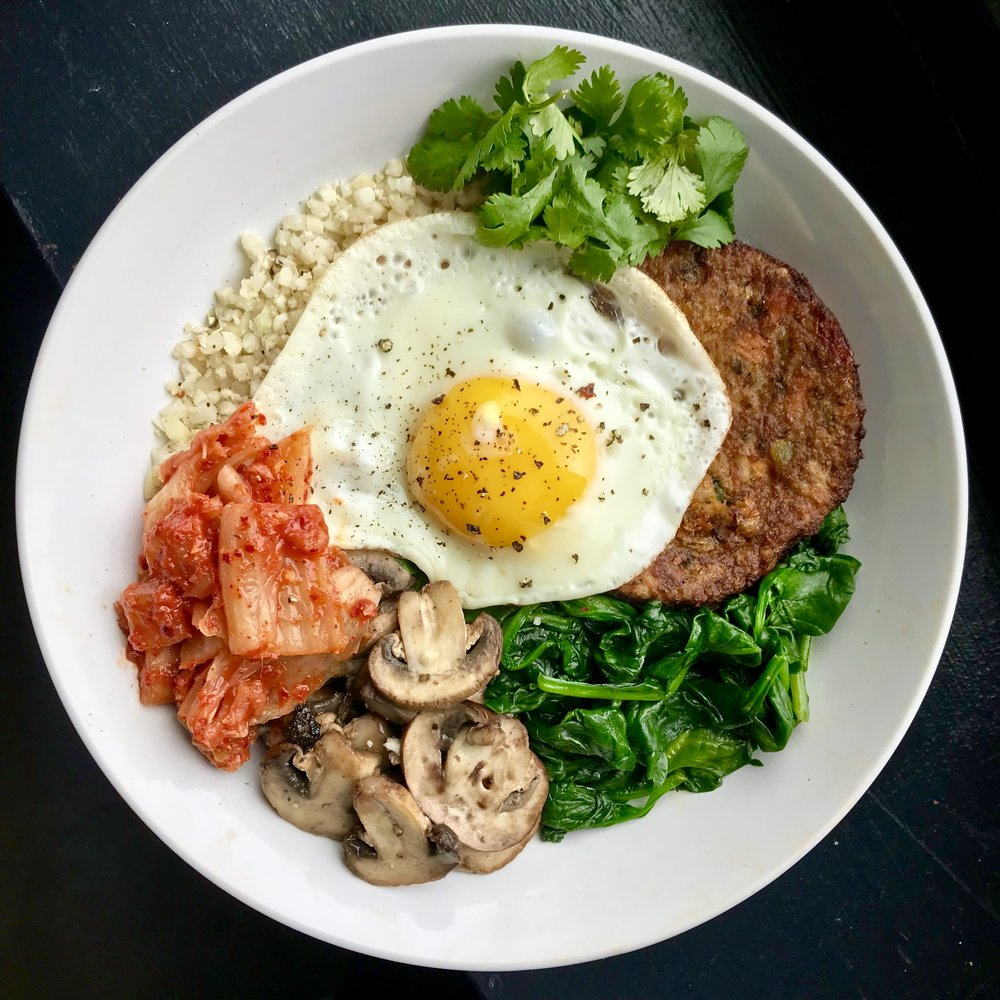 If there is a bibimbap bowl on a restaurant menu there is a 99% chance that I will be ordering it. There's  something about a big bowl of crispy rice, savory veggies, tangy pickles and a runny egg that I cannot resist (my mouth is watering just typing this).   This is not your traditional bibimbap, but I might like this lightened up version even better!  We've got garlicky cauliflower rice, sautéed veggies, a crispy fried egg, spicy kimchi, cilantro and a major flavor boost from the Asian veggie burger.  The best part: it takes just 15 minutes to cook from start to finish with the help of a couple short-cuts (like pre-riced cauliflower and a frozen Dr. Praeger's veggie burger).