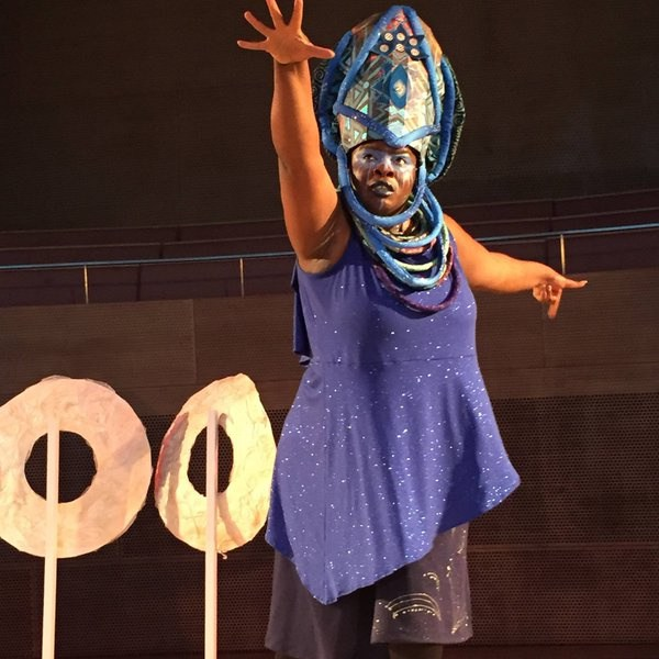 """Image from """"Ma(s)king Her"""" by Honey Pot Performance at Pritzker Pavilion, Millennium Park, Chicago, April 14–16, 2016 . Featuring """"Oracle"""" sculptures and Abra Johnson as Wonder in headdress, both designed by D. Denenge Akpem (featuring textile by Euzhan Sims and costume by Jane Bagnall). Image credit: Lani Montreal."""