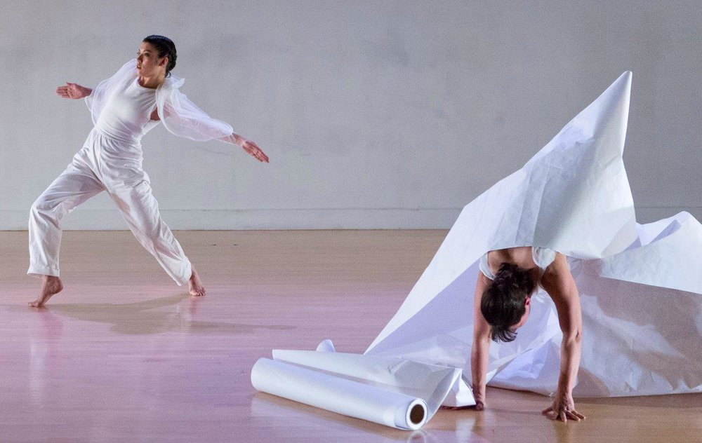 Two dancers in white costumes performing at Links Hall. Image courtesy of Links Hall.