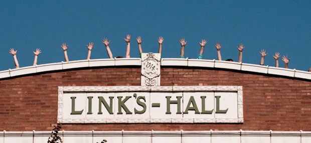 Facade of the original Links Hall building, built in 1914, with tiled signage and people standing with their arms in the air along the roofline. Image courtesy of wbez.org.