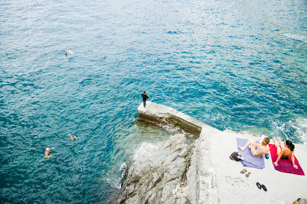 "Italy, Cinque Terra. A woman (center) wears a ""burkini"" while other vacationers play in the water or relax in the sun. In 2016 France drew international attention by banning the burkini, a swimsuit designed to respect Islamic traditions, whereas Italy rejected a similar ban proposed that same year."