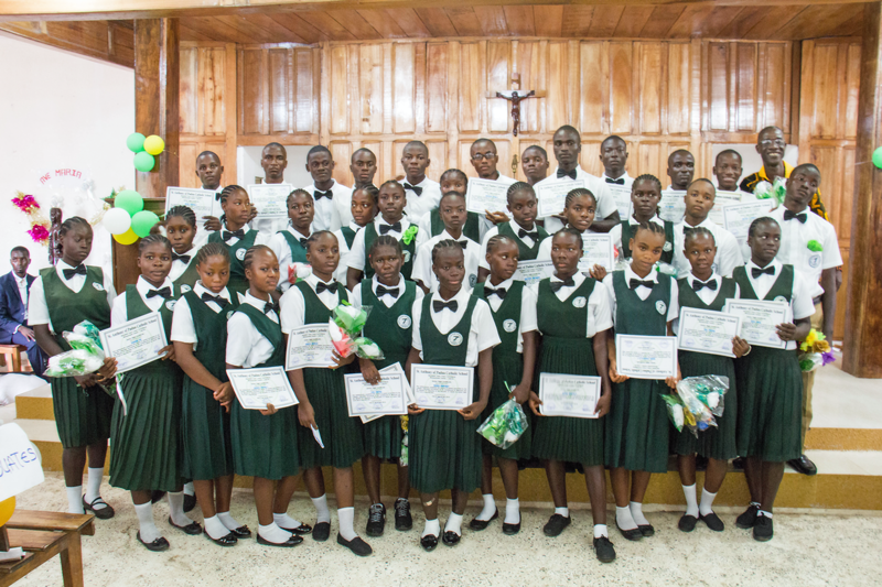 St. Anthony students pose with their certificate and flower bouquets in our chapel.