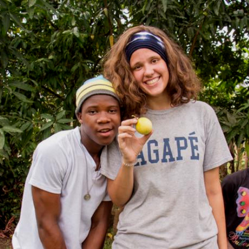 Claire picking fruit on Liberia Mission's farm.