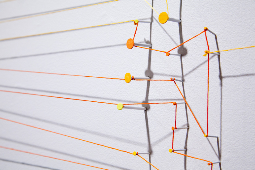 "detail from shadow drawing (red-orange-yellow) , 2010 nails, acrylic, thread and shadow on wall 62 x 118"" (dimensions variable)"