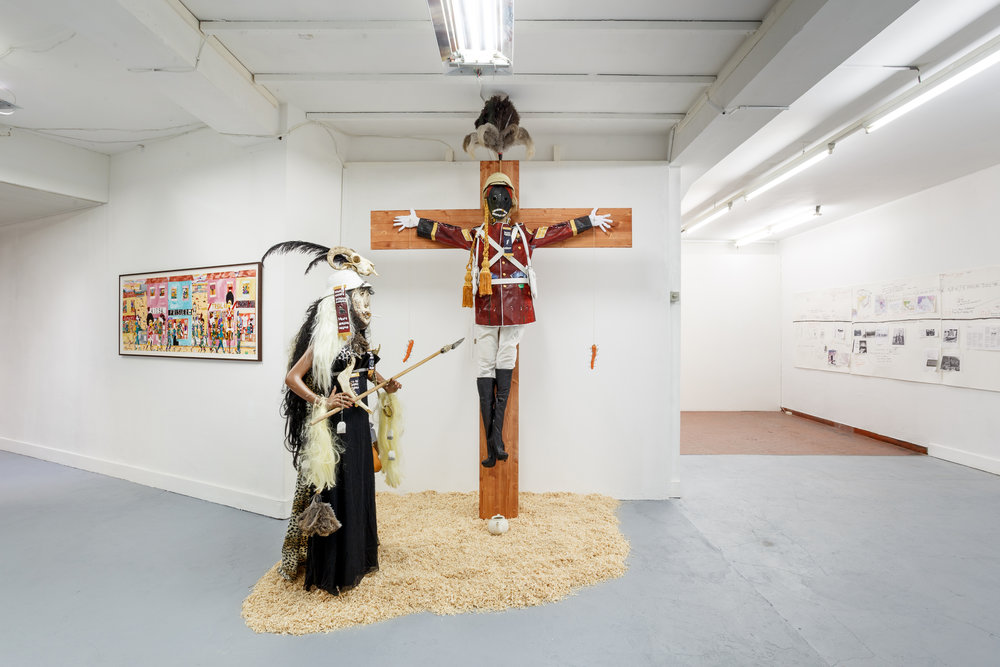 Installation view,  6. Sam Durant & Andrew Gilbert , Last Tango, Zurich, 2017. Center: Andrew Gilbert,  ´T  he Eternal Idol   –   British   Officer Crucifi  ed, 8th Xhosa War   – 1853´ , 2017, mixed media, dimensions variable Left: Andrew Gilbert,´ Saint Andrew lives in Ooooooogily Street - not in contemporary disgusting Berlin  ´ , 2016, acrylic, watercolor and fineliner on paper, 70 x 200 cm Right: Sam Durant,  Working Drawing for Nonaligned Research , 2013-ongoing, mixed media collage, 5 parts: 139 x 134 cm; 135 x 134 cm; 181 x 133 cm; 141 x 134 cm; 163.5 x 134.5 cm Photo: Kilian Bannwart