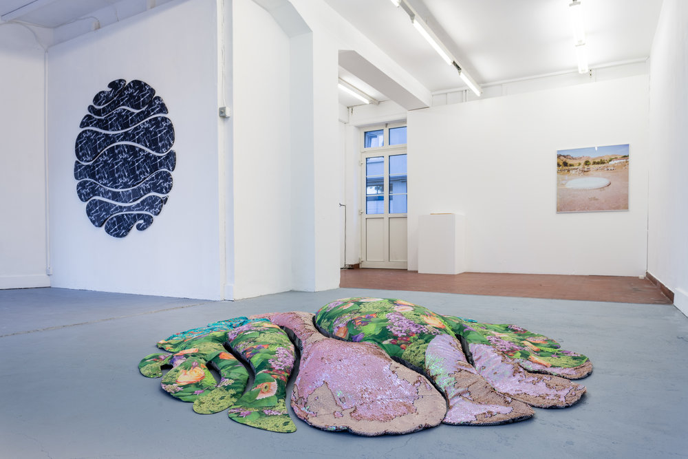 Installation view, 5. Donatella Bernardi & Wong Ping Left: Donatella Bernardi,  Elegant Sagging , 2017, digital printed fabric, shaped canvas, 175 x 175 cm Centre: Donatella Bernardi,  Carpet Pond , 2017, textiles (cotton, sequins and polyester), 240 x 240 x 27 cm Back: Donatella Bernardi,  Portique Syrien Series 4 , inkjet print mounted on aluminium board, 101 x 100.5cm Photo: Kilian Bannwart