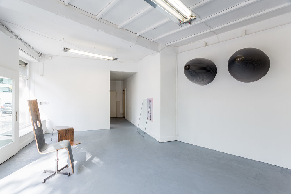 Far Left: Fiona Banner,  Pinstripe Chair,  2015, graphite, vinyl, plywood, chair base, 148 x 52 x 50 cm Left: Fiona Banner,  Pinstripe Chair , 2015, graphite, vinyl, plywood, chair base, 43.3 x 149 x 46.2 cm Centre: Peter Voss-Knude,  Tuning Fork , 2017, oil pastel on reflective paper, 64.5 x 90 cm Right: Fiona Banner,  Nose Art , 2015, harrier jump jet nose cones, graphite, 107 x 79 cm each Photo: Kilian Bannwart