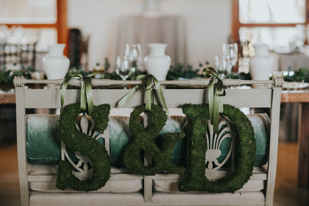 """We used my parents' antique settee at the head table for myself and David, and decorated it with moss """"S"""" and """"D"""" letters, to echo the moss chargers."""