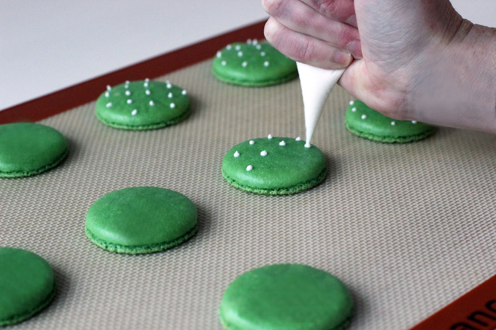 Step 2: Pipe spines onto larger and darker green macaron shells.
