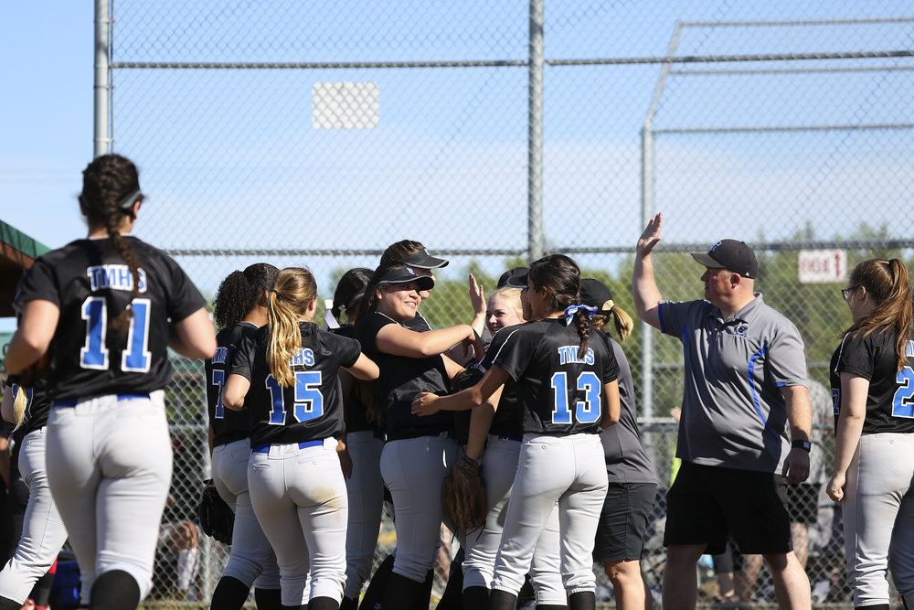 The Thunder Mountain softball team surrounds their pitcher, Nina Fenumiai (4) (center) on the field in celebration after the second inning with high fives and loud cheers in a game against Juneau Douglas on Saturday, June 3rd at the Softball State Championships in the South Davis Park Complex in Fairbanks, AK. Sarah Manriquez/ Juneau Empire