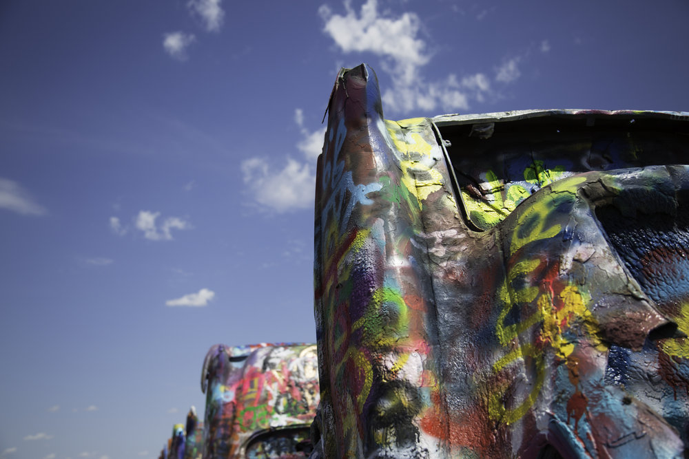 "he Cadillac Ranch is a public art installation put into place in 1974 by Chip Lord, Hudson Marquez and Doug Michels. They used older, ""junk"" cadillacs that represented the evolution of the car line from 1949 to 1963. The vehicles were half buried into the ground at an angle that corresponded to that of the Great Pyramid of Giza in Egypt."