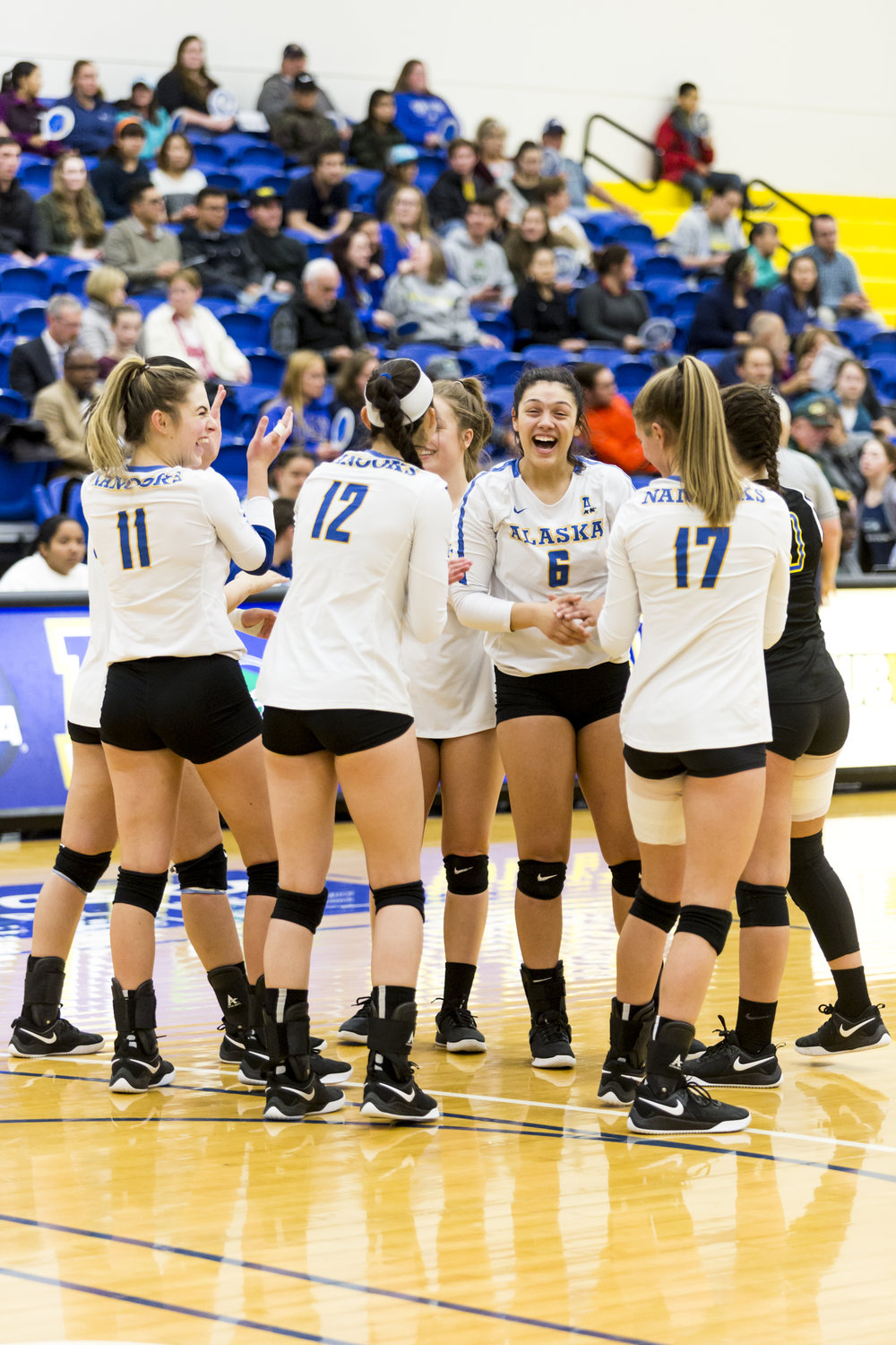 The 2018 UAF Women's Volleyball starting line up breaks into laughter after their a team cheer on the court before the start of the game on Tuesday, October 9th, 2018 UAF vs UAA.