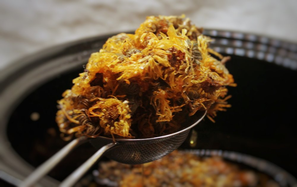 Remove calendula and lavender from oil using mesh strainer