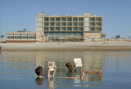 Bathers read magazines near shoreline while floating in the Dead Sea. December, 1964.