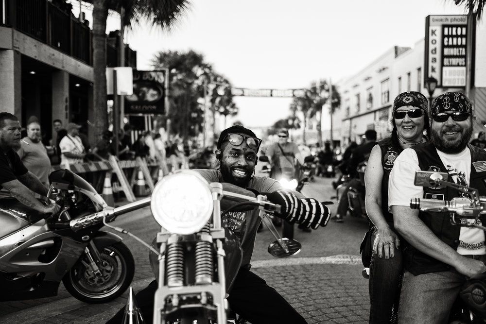 Snapshot of smiling bikers riding down the street. Pedestrians gathered and watching from either side of the street. Bike Week 2017.
