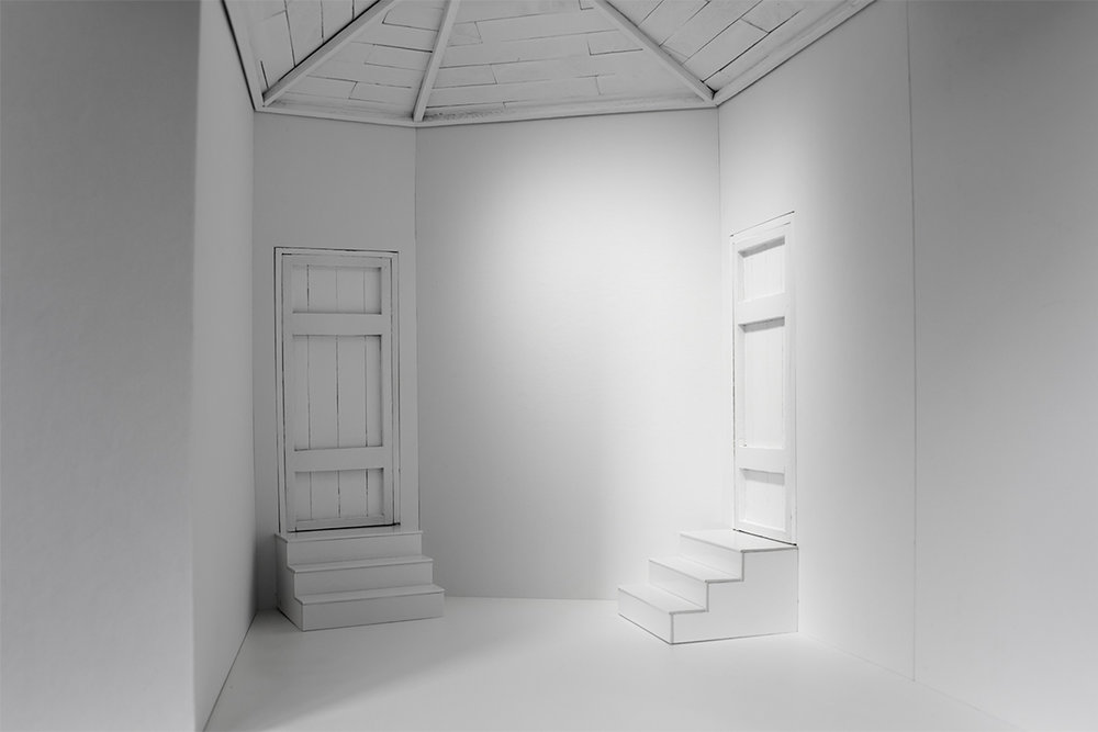 The interior of a model, showing a room with two sets of stairs each leading to a closed door