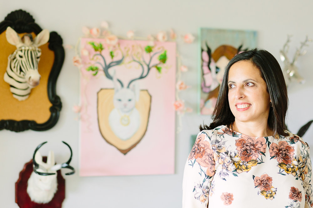 Rana at home in front of her whimsical paintings.