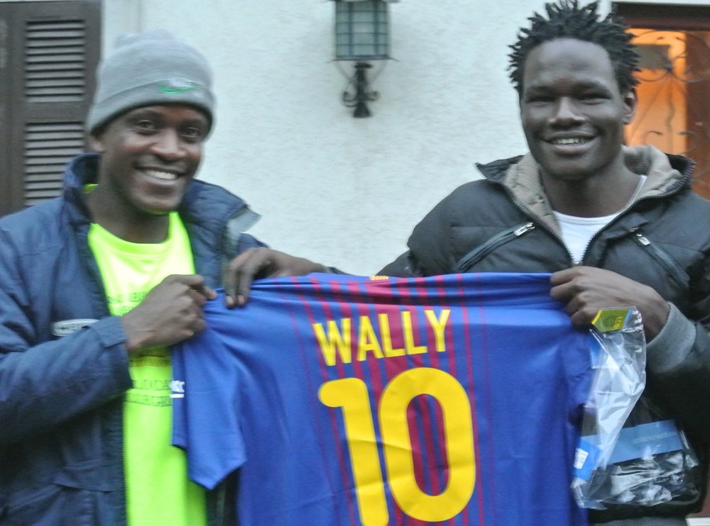 Sama (L) with Wally (R) and his Barca jersey at their housing in Bergamo province, November 2017.