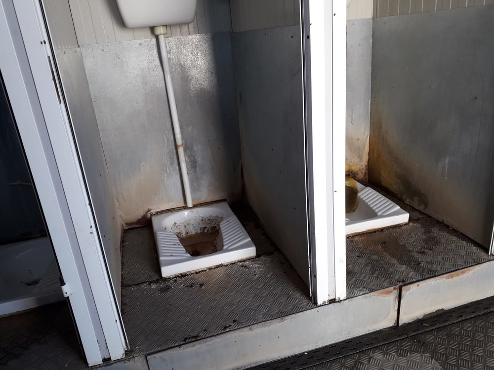 Bathroom stalls without doors and dirty toilets at the housing camp near Foggia, Italy. July, 2018. © Pamela Kerpius