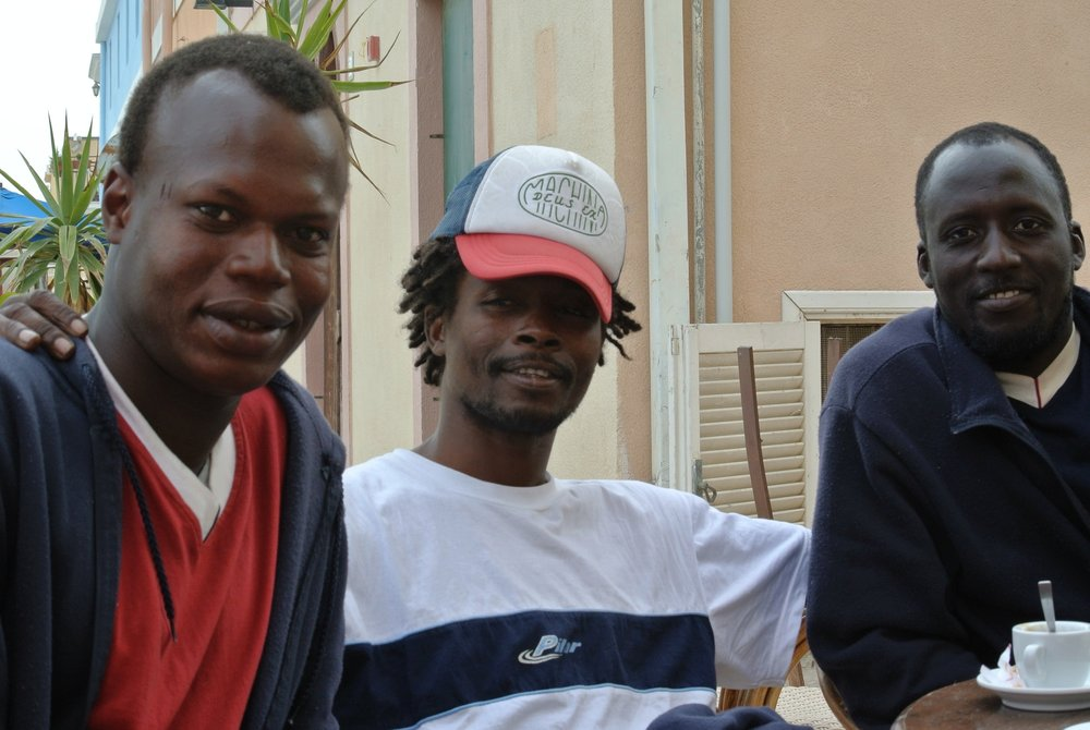 Friends: (L to R) Yoro,  Ousman  wearing my cap, and  Baboucarr . April 28, 2017, Lampedusa.