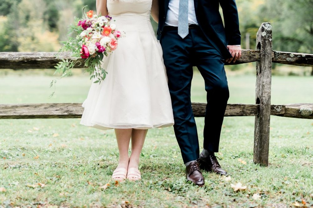 3 bride and groom against a fence.jpg