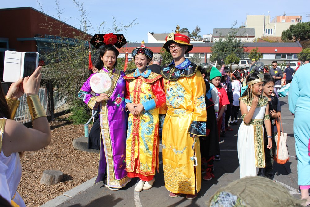 Ms. Wang (K), Ms. Zhou (3rd), and Mr. Li (3rd), getting their photographs taken at the 2018 Halloween parade with an online-capable device!