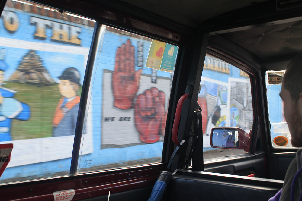 Driving by murals depicting justice movements around the world near the Catholic part of Belfast.