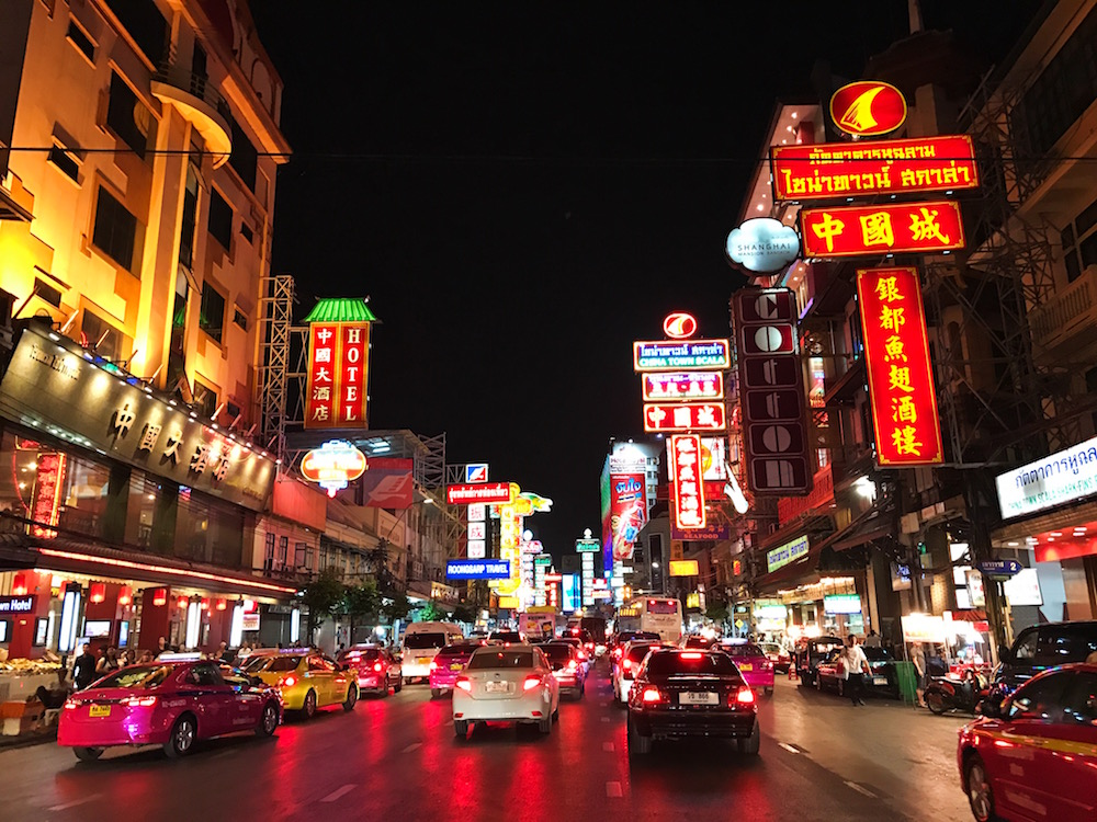 Chinatown at night is filled with neon signs and sidewalk restaurants.