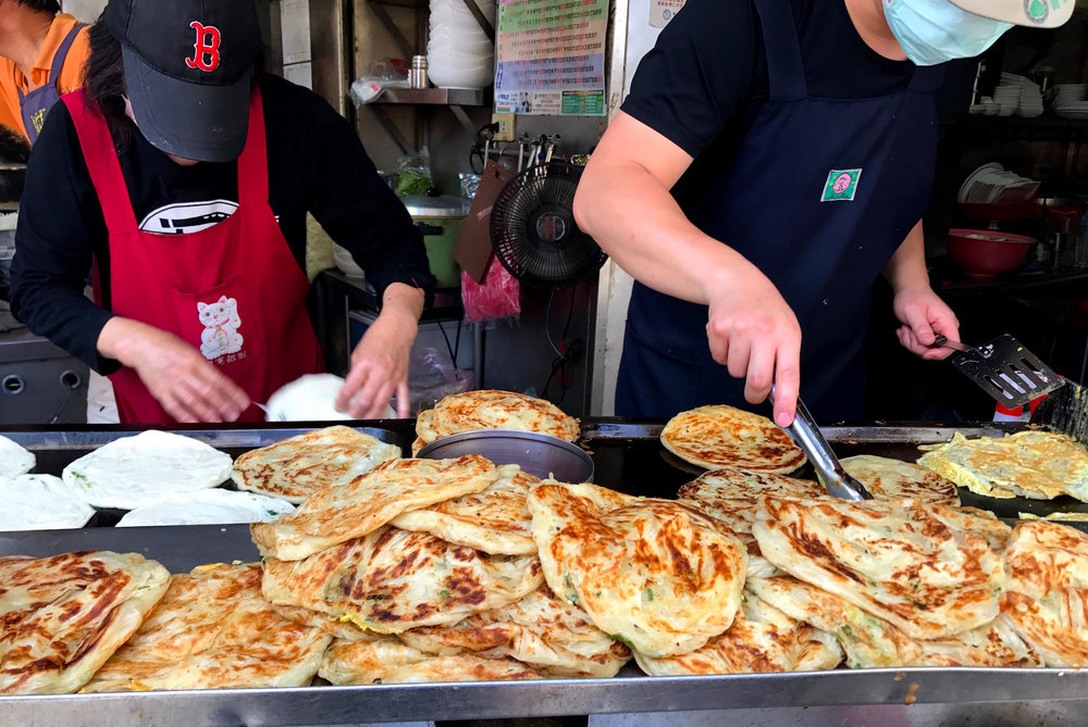 Scallion pancakes are delicious and customizable. You can add ingredients like ham, cheese, egg, and Taiwanese basil.