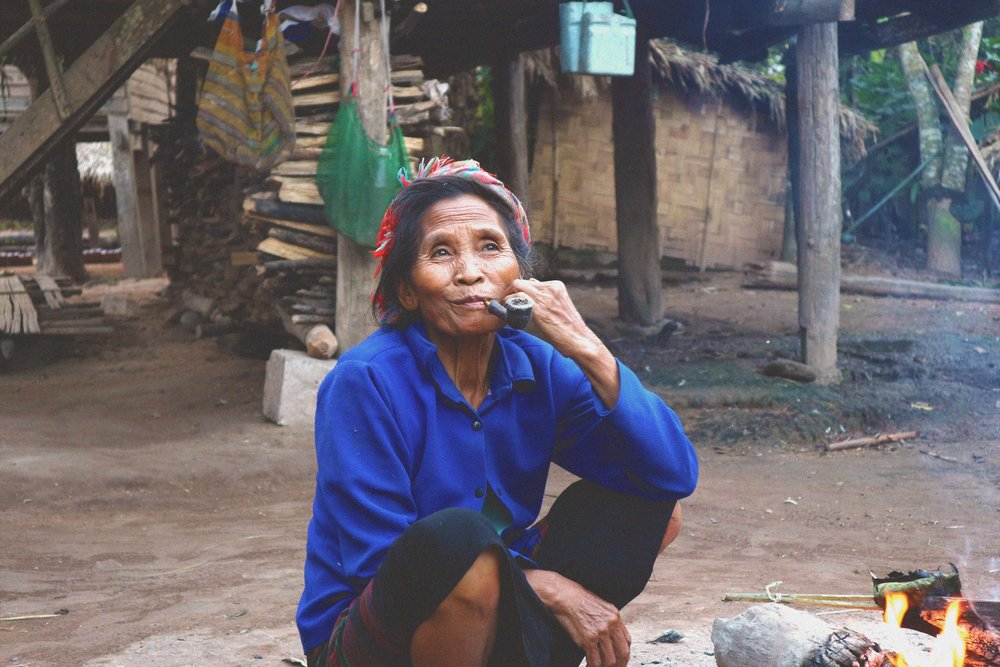 Old lady smoking tobacco by a fire.  They say the smoke keeps the mozzies away.