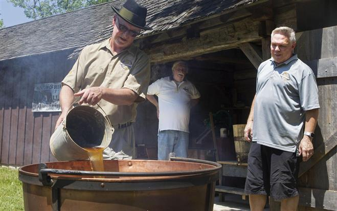 Tim Murphy (from left) pours a sugary malted solution into a kettle to be boiled while Gary Luther and Bob Heger watch at Old World Wisconsin in Eagle. More at jsonline.com/photos . Credit: Sam Caravana
