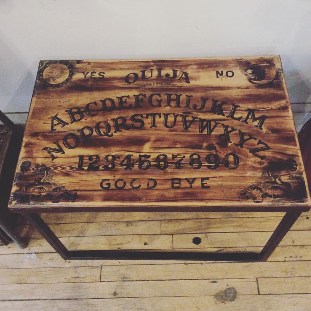 $225 Horror lovers small Ouija board coffee table. Reclaimed wood top with a metal base. Hand painted with beautiful illustrations in each corner. Sold.