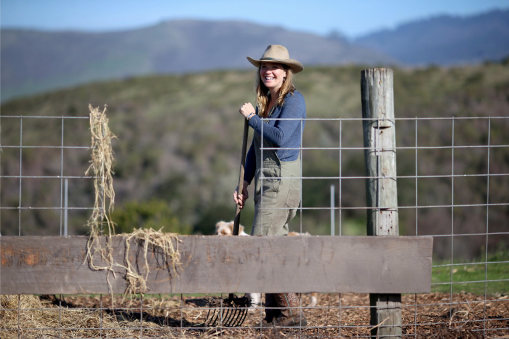 Doniga Markegard pauses while shoveling wood chips and hay, into a pen with piglets and their mother, at the Markegard Family Grass-Fed Ranch.