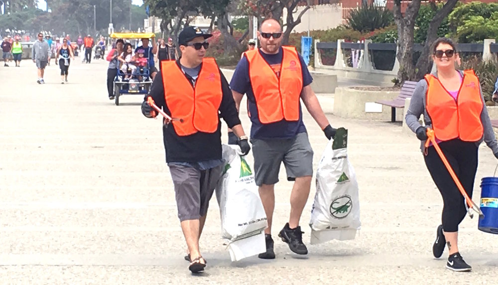 three VOLUNTEERS walk the promenade during a beach cleanup on june 24.