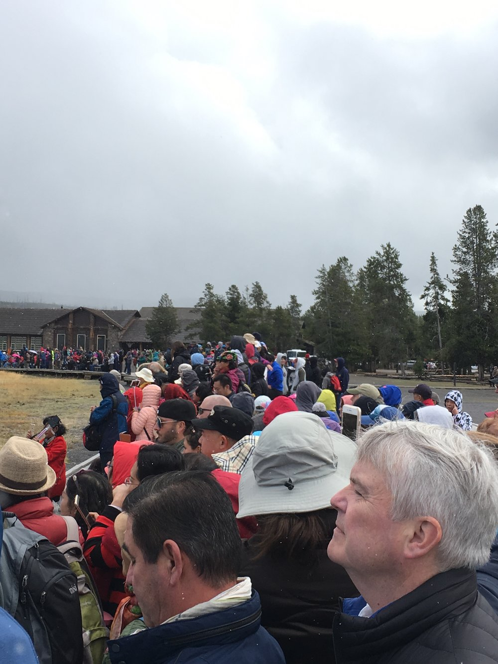 On a cold, rainy, misty, snowy day, there were a lot of people on hand to watch the 1:22 pm performance of Old Faithful.  The viewing area is about 300 feet from the geyser, and pretty much encircles the geyser.  The platform was packed all the way around 4 and 5 people deep.  As we stood waiting for the start, I kept wondering where all of these people had come from.
