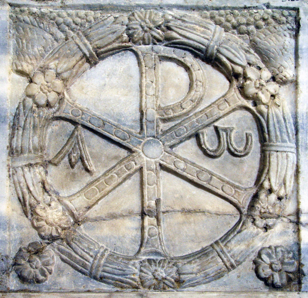 According to legend Constantine had positioned his army opposite the army of Maxentius. The night before the battle Constantine had a vision in which he was told to place the sign of God on the shields of his men and his army would be led to victory. The next more Constatine had the ChiRho placed on the shield of his men and with the start of the battle the fight quickly became a rout. Maxentius was drowned while trying to cross the Tiber River in his escape back to Rome. The Kerch Missorium shows Constantine's son Constantius II, accompanied by a guardsman with the  Chi Rho  monogram depicted on his shield. Photograph is taken from Ludwig von Sybel,  Christliche Antike , vol. 2, Marburg, 1909
