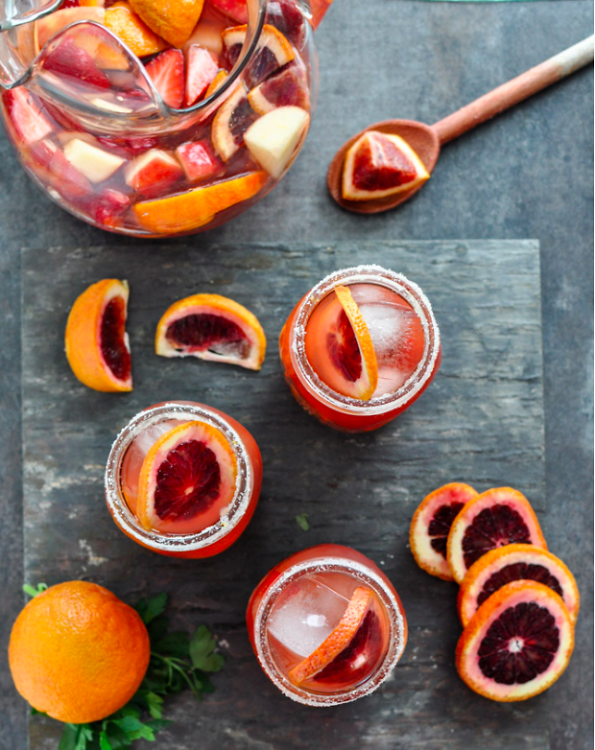 """For this specialty sangria recipe, the key to an authentic Spaniard approved staple is Campo Viejo's Garnacha Red Wine. The wine's fruity, spicy flavor, all for $11, is the perfect ingredient for this refreshingly sweet cocktail.  Recipe:  2 bottles of Garnacha Red Wine  3 cups Blackberries  6 Blood Oranges, wedged  1 Apple, chopped  2 cups Strawberries, sliced  2 Cinnamon Sticks  1 cup Sugar  1 cup club soda  1 cup Smirnoff Vodka  Ice  Directions:  1. Zest one of the blood oranges and combine with 1/2 cup of sugar in a small bowl  2. Juice 3 of the oranges, chop remaining 3 into pieces 3. In large pitcher, place all of the sliced fruits in the pitcher, muddle 4. Pour remaining sugar over the muddled fruits- add wine, vodka, club soda over fruits 5. Dunk each glass in """"orange-zest"""" sugar, pour sangria over ice, serve  *For even more flavor, refrigerate for at least two hours before serving*   [via  Howsweeteats.com ]"""