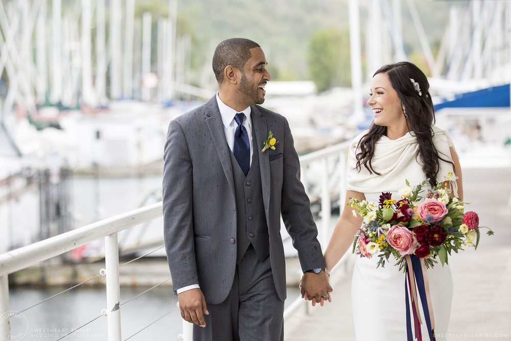 A happy, natural moment between a mixed race bride and groom, laughing and walking down the deck at Bluffer's Park Marina, with boats and the Bluffs in the background.