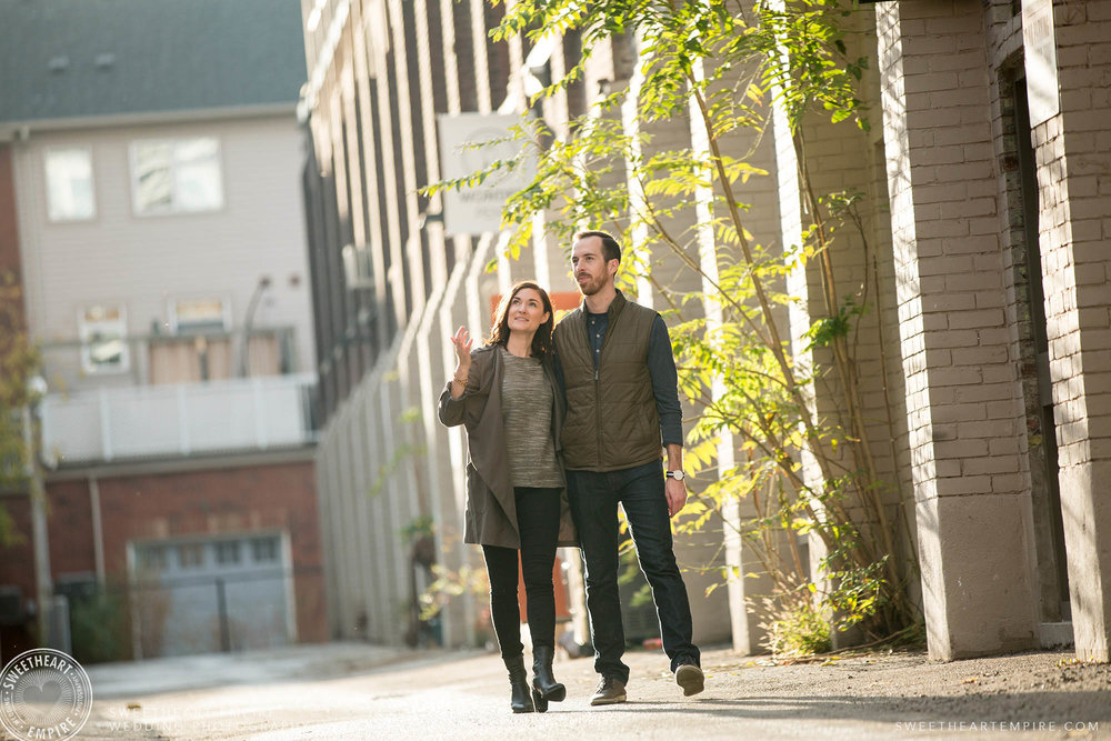 Couple holding hands walking in a sunny alleyway, Leslieville engagement photos