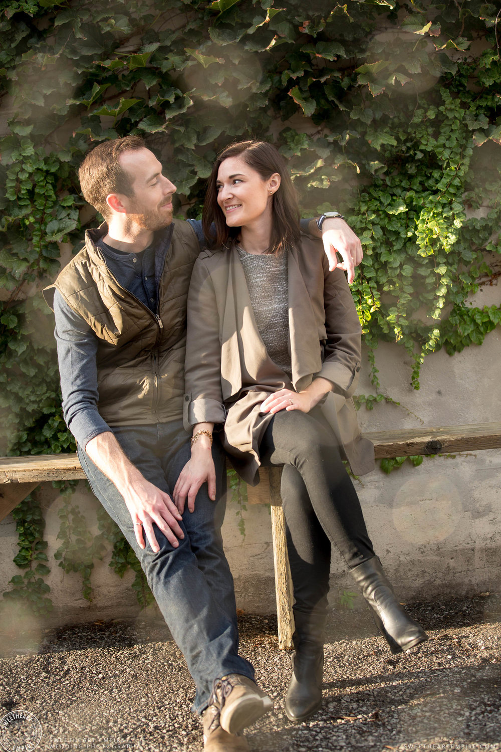 In-love couple looking at one another sitting in front of ivy wall, Leslieville engagement photos