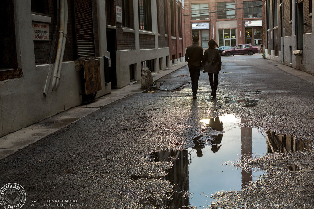 Reflection of a couple in a puddle as they walk away, Leslieville engagement photos