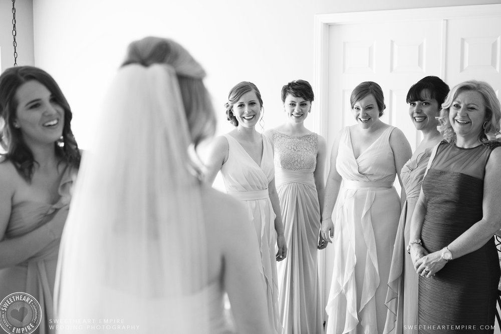 Bridesmaids and mother of the bride seeing Vanessa in her wedding gown and veil for the first time.