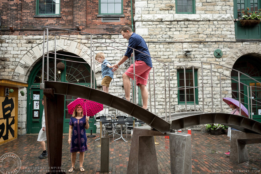 02_Father & toddler son climbing on sculptures in distillery district while concerned mom watches.jpg