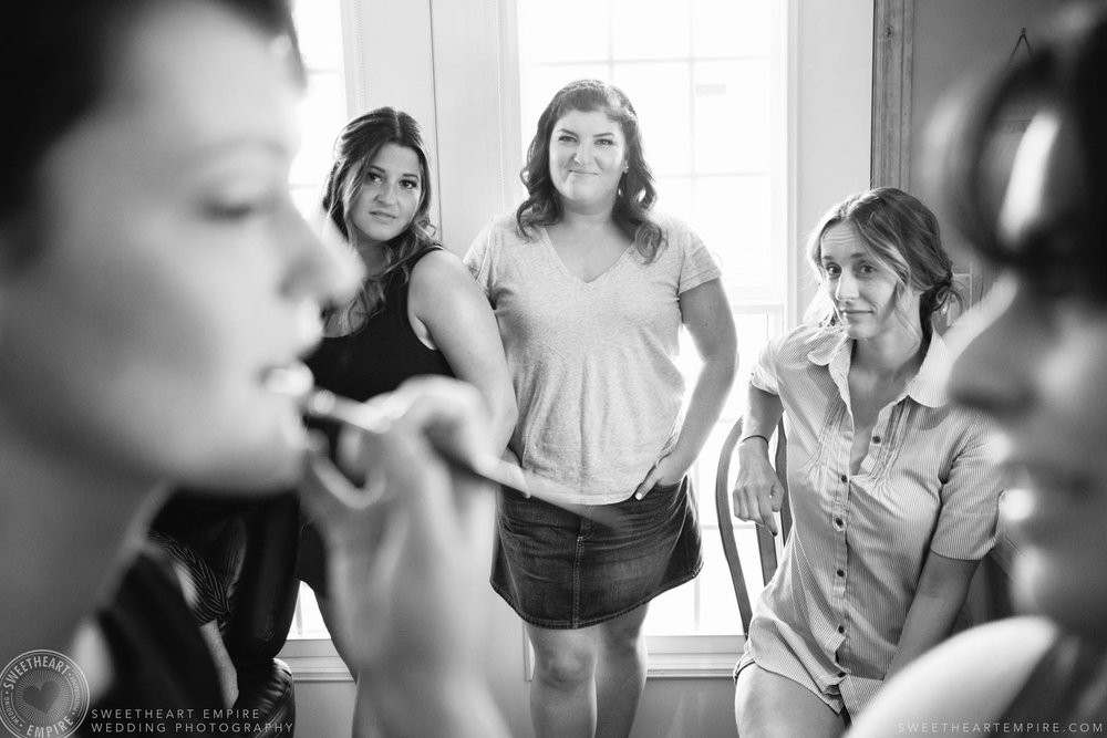 Friends watching bride getting her makeup done.