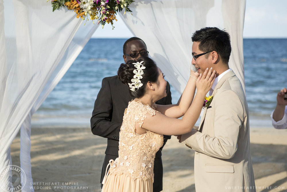Bride wiping grooms tears; Iberostar Grand Hotel Rose Hall, in Montego Bay, Jamaica