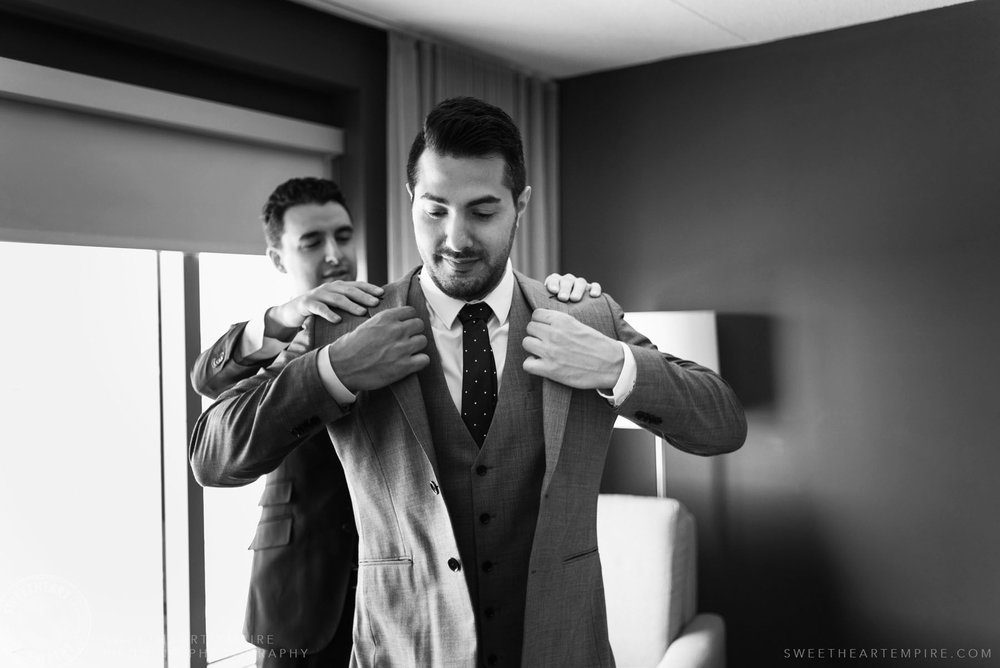 Best man helping groom get dressed; Eagles Nest Golf Club Wedding Photos