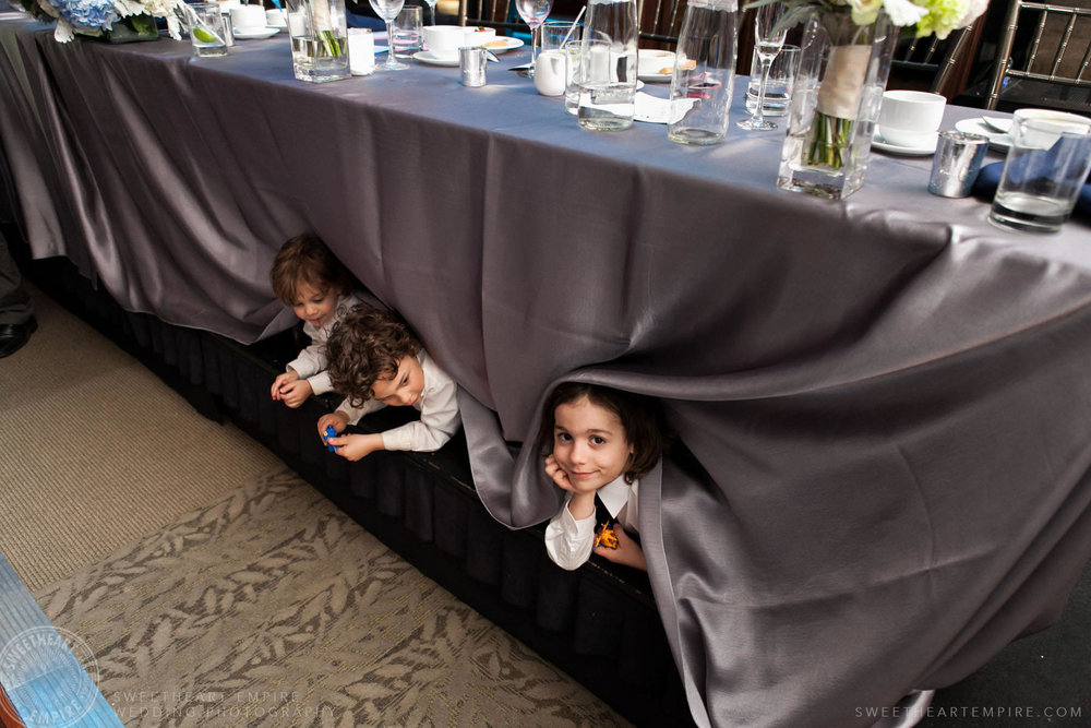 Kids hiding under bride and groom's table; Eagles Nest Golf Club Wedding